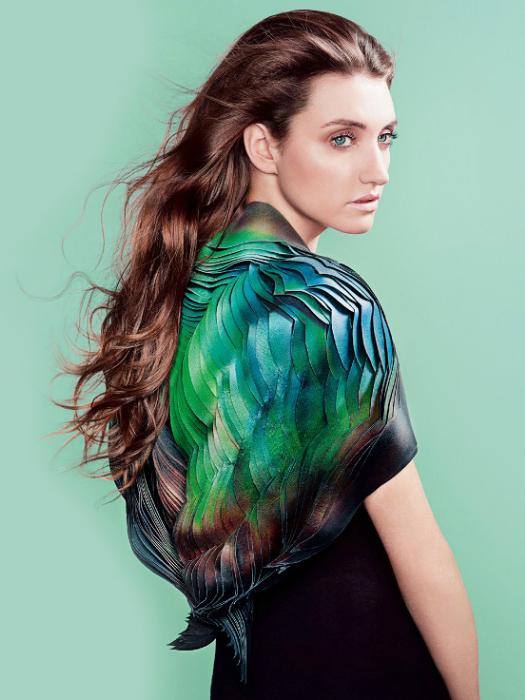 Дизайнер Лорен Боукер создала платье, которое реагирует на порывы ветра и лучи солнца. Изделие обработано жидкими кристаллами и мультисенсорными красками, которые меняют цвет и переливаются всеми цветами радуги под воздействием силы трения.